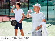 mature man and young man drink water on padel court. Стоковое фото, фотограф Татьяна Яцевич / Фотобанк Лори