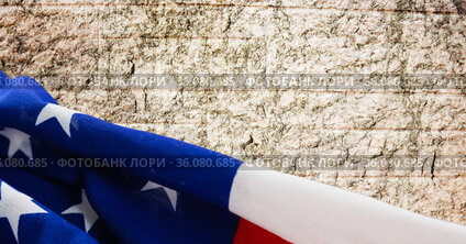 Composition of american flag over rough pale stone wall