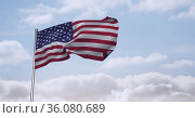 Composition of billowing american flag on flagpole over cloudy blue sky. Стоковое фото, агентство Wavebreak Media / Фотобанк Лори