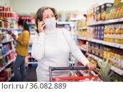 Elderly woman in protective mask talking on phone in grocery supermarket. Стоковое фото, фотограф Яков Филимонов / Фотобанк Лори
