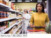 Hispanic woman walking with shopping trolley in grocery shop. Стоковое фото, фотограф Яков Филимонов / Фотобанк Лори