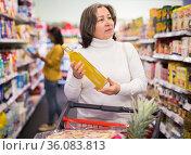 Pensive elderly woman choosing vegetable oil in supermarket. Стоковое фото, фотограф Яков Филимонов / Фотобанк Лори