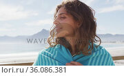 Portrait of happy mixed race woman standing by the sea with blanket over shoulders smiling. Стоковое видео, агентство Wavebreak Media / Фотобанк Лори