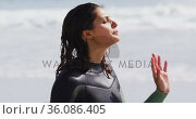 Happy mixed race woman in wetsuit standing on beach looking out to sea. Стоковое видео, агентство Wavebreak Media / Фотобанк Лори