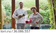 Portrait of mixed race couple standing together holding yoga mats at vacation home. Стоковое видео, агентство Wavebreak Media / Фотобанк Лори