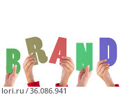 Composition of hands holding colourful letters, spelling out the word brand, on white. Стоковое фото, агентство Wavebreak Media / Фотобанк Лори