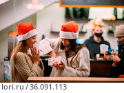 The girl gives a gift to her female friend in caffe. Portrait of happy... Стоковое фото, фотограф Zoonar.com/Oleksii Hrecheniuk / easy Fotostock / Фотобанк Лори