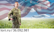 Composition of soldier holding helmet against meadow and american flag. Стоковое фото, агентство Wavebreak Media / Фотобанк Лори