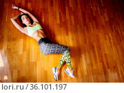 Attractive fitness woman tired after workout in gym lays on floor... Стоковое фото, фотограф Zoonar.com/KYRYLO SHEVTSOV / easy Fotostock / Фотобанк Лори