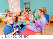 Young attractive teacher helping small kids to be engaged into their... Стоковое фото, фотограф Zoonar.com/OKSANA SHUFRYCH / easy Fotostock / Фотобанк Лори