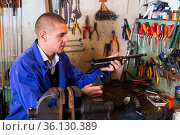 Gunsmith assembling smallbore sporting pistol in workshop. Стоковое фото, фотограф Яков Филимонов / Фотобанк Лори