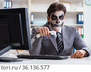 Businessmsn with scary face mask working in office. Стоковое фото, фотограф Elnur / Фотобанк Лори
