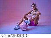 Sportswoman with ball sitting on floor in studio. Стоковое фото, фотограф Tryapitsyn Sergiy / Фотобанк Лори