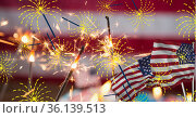 Composition of sparklers and flags over american flag. Стоковое фото, агентство Wavebreak Media / Фотобанк Лори