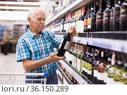 mature senor choosing alcoholic drinks in supermarket. Стоковое фото, фотограф Татьяна Яцевич / Фотобанк Лори