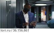 Portrait of african american businessman wearing face mask using tablet in modern office. Стоковое видео, агентство Wavebreak Media / Фотобанк Лори