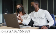 Diverse businessman and businesswoman wearing face masks discussing and using laptop in office. Стоковое видео, агентство Wavebreak Media / Фотобанк Лори