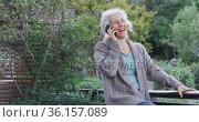 Portrait of senior mixed race woman talking on smartphone on balcony. Стоковое видео, агентство Wavebreak Media / Фотобанк Лори