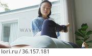Asian female physiotherapist holding leg of female patient lying on examination bed at surgery. Стоковое видео, агентство Wavebreak Media / Фотобанк Лори