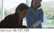 Smiling asian female doctor helping senior female patient to walk using walking frame. Стоковое видео, агентство Wavebreak Media / Фотобанк Лори