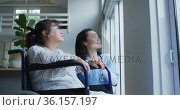 Smiling asian female doctor looking out of window and talking with female patient in wheelchair. Стоковое видео, агентство Wavebreak Media / Фотобанк Лори