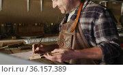 Caucasian male knife maker in workshop holding tool and making notes. Стоковое видео, агентство Wavebreak Media / Фотобанк Лори