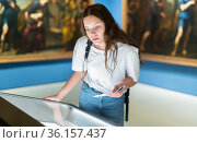 Attentive girl visitor at the museum looks at the exposition behind a glass display case. Стоковое фото, фотограф Яков Филимонов / Фотобанк Лори