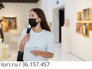 Young girl wearing a protective mask in the museum looks at the exhibits. Стоковое фото, фотограф Яков Филимонов / Фотобанк Лори