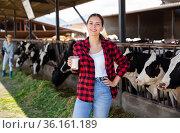Young woman farmer working at dairy farm. Стоковое фото, фотограф Яков Филимонов / Фотобанк Лори