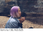 Portrait of a teenage girl hiker sits with a mug on the river bank looking at the coastal cliffs. Стоковое фото, фотограф Евгений Харитонов / Фотобанк Лори