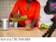 African american woman in kitchen pouring health drink, making vlog using laptop and camera. Стоковое фото, агентство Wavebreak Media / Фотобанк Лори