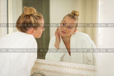 Caucasian woman in bathroom wearing bathrobe, looking in mirror and moisturising face