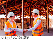 Attractive young woman engineer shaking hand with professional builder... Стоковое фото, фотограф Zoonar.com/Oksana Shufrych / easy Fotostock / Фотобанк Лори