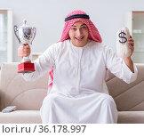 Arab man with prize and money on sofa. Стоковое фото, фотограф Elnur / Фотобанк Лори