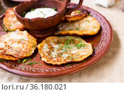 belarusian draniki with sour cream and herbs in a restaurant. Стоковое фото, фотограф Татьяна Яцевич / Фотобанк Лори