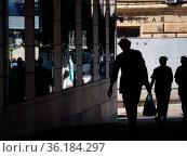 Силуэты мужчины с пакетом из гастронома и двух молодых людей у стены с зеркальными стеклами. Редакционное фото, фотограф Сайганов Александр / Фотобанк Лори