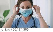 Portrait of caucasian female doctor wearing face mask at home. Стоковое видео, агентство Wavebreak Media / Фотобанк Лори