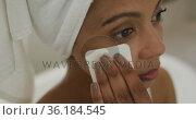 Mixed race woman wearing towel on head cleaning her face. Стоковое видео, агентство Wavebreak Media / Фотобанк Лори
