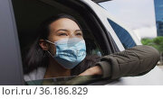 Asian woman wearing face mask looking out of the window while sitting in the car. Стоковое видео, агентство Wavebreak Media / Фотобанк Лори