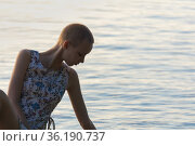 Portrait of a teenage girl with a short haircut in a dress on a background of open water. Стоковое фото, фотограф Евгений Харитонов / Фотобанк Лори