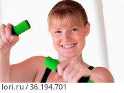 Young happy girl doing dumbbell exercises at home. Стоковое фото, фотограф Zoonar.com/Wolfgang Zwanzger www.20er.net / easy Fotostock / Фотобанк Лори