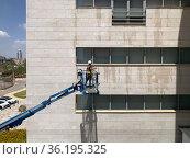 Window cleaner at height. Редакционное фото, фотограф Irina Opachevsky / Фотобанк Лори