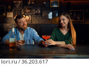 Couple with alcohol gets acquainted in bar. Стоковое фото, фотограф Tryapitsyn Sergiy / Фотобанк Лори