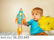 Toddler boy play astronaut holding paper rocket. Стоковое фото, фотограф Сергей Новиков / Фотобанк Лори