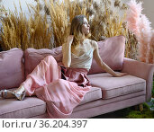 Young adult woman sitting on a sofa in a room in tall grass. Стоковое фото, фотограф Алексей Кузнецов / Фотобанк Лори