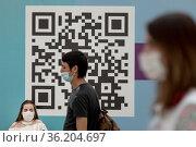 Люди ждут очереди в центре вакцинации на фоне QR-кода в городе Москве, Россия. Редакционное фото, фотограф Николай Винокуров / Фотобанк Лори