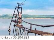 Girl with a short haircut stands on a rustic water intake against the backdrop of a river in the sun. Стоковое фото, фотограф Евгений Харитонов / Фотобанк Лори