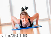 Happy young girl doing pushups exercises on the floor at home. Стоковое фото, фотограф Zoonar.com/Wolfgang Zwanzger www.20er.net / easy Fotostock / Фотобанк Лори