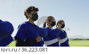 Diverse team of female baseball players in face masks standing in line with hands on hearts. Стоковое видео, агентство Wavebreak Media / Фотобанк Лори