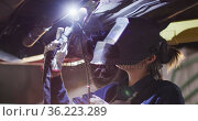 Female mechanic wearing welding helmet welding under a car at a car service station. Стоковое видео, агентство Wavebreak Media / Фотобанк Лори